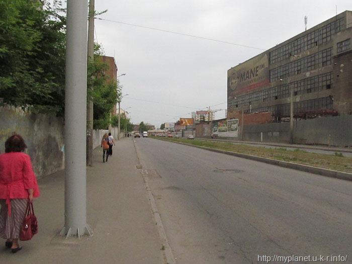 Пустынная промышленная улочка и пара пешеходов на ней