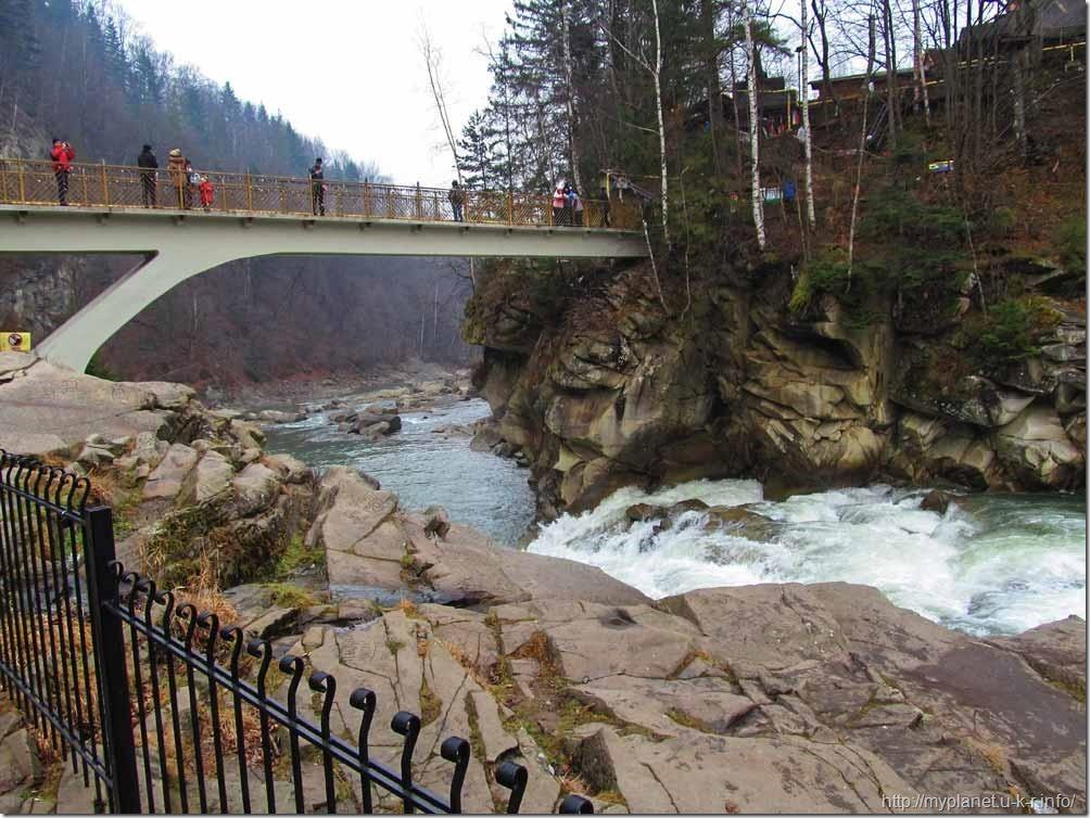 Туристи на мосту над водоспадом Пробій