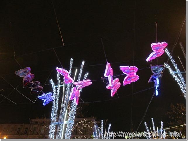Сказочные светящиеся бабочки над головой у входа в парк иллюминаций