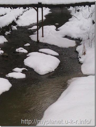 Полузамерзшая горная река-ручей возле остановки в Буковели