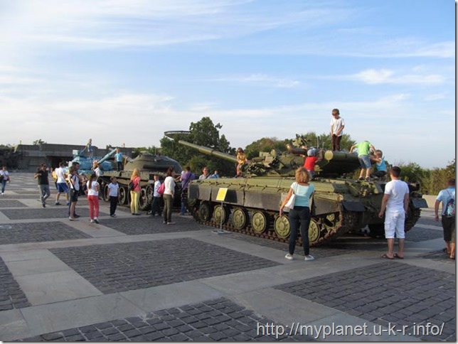 Tourists with children gathered around the tanks