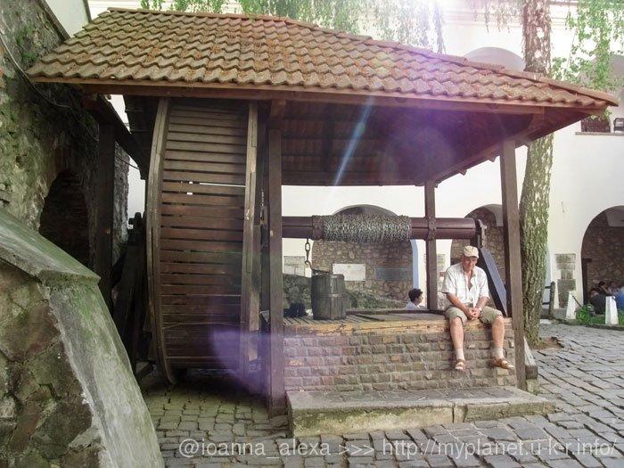 Дедуля-турист отдыхает возле старинного колодца в Мукачевской крепости