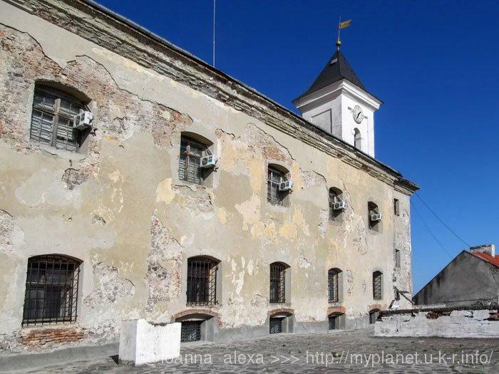 Вид на обшарпанную стену древнего замка с современными кондиционерами в окнах