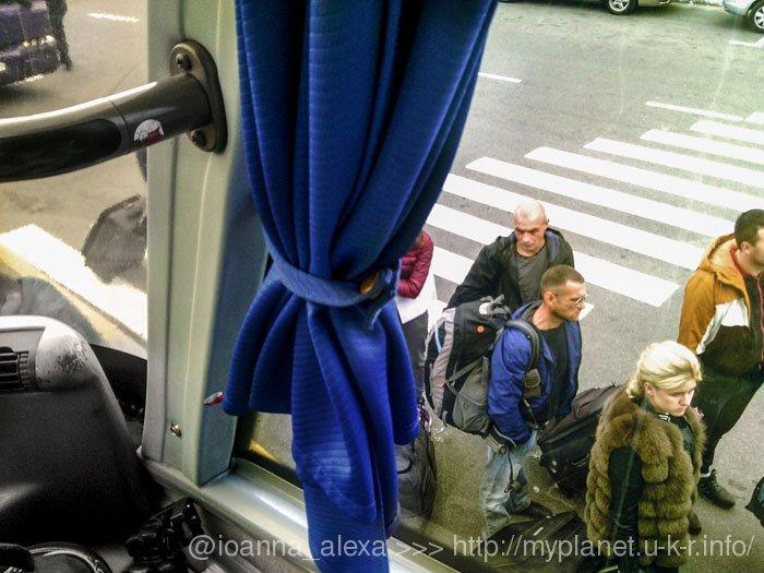 Пасажири під час посадки в автобус — вид з бокового вікна