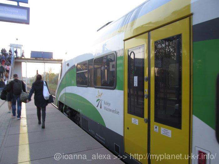 Люди на перроне станции спешат из электрички пересесть на автобус в аэропорт Варшава-Модлин Мазовия