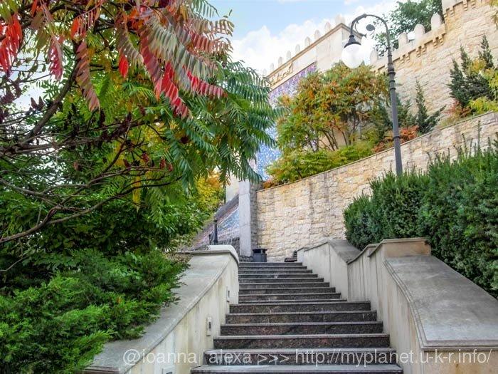 Красиві алеї та копія старовинної кріпосної стіни серед зелені в сквері