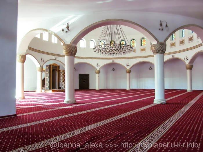 Молитвенный зал мечети Ар-Рахма с красными коврами и белыми стенами