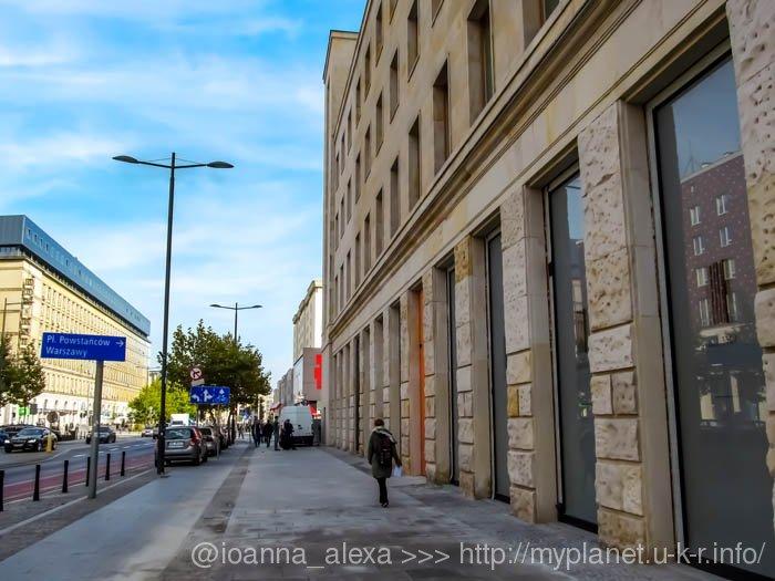 Чистая, идеально уложенная, светло-серая тротуарная плитка возле бежевых стен старинных зданий создает впечатление пространства