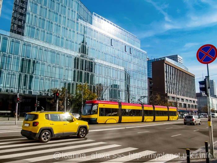 Яркие желтые современные трамваи на фоне стеклянных зданий